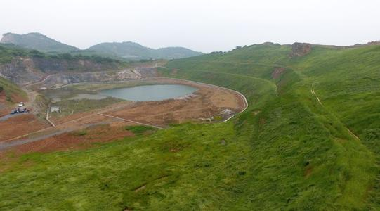 """""""矿山复绿""""是指通过采用工程、生物等技术手段对因矿山开采引起的地质环境问题进行综合治理,使矿山地质环境达到稳定、生态环境得以恢复的过程。  矿山复绿的主要技术方法 现阶段,我国矿山地质环境治理中常采用的矿山复绿技术方法主要有覆土绿化、挡墙蓄坡绿化、开凿平台绿化、边坡钻孔绿化、鱼鳞坑蓄土绿化、挂网喷播绿化、生态袋绿化、生态草毯绿化、飘台绿化、植生混凝土绿化等。  1 覆土绿化  对矿山开采后形成的面积较大、比较平坦的矿场或其他较为平整的场地,经地形测量后,进行场地的挖填设计,控制土地高程,确定出土地边界,对土地进行平整,配土覆土,根据恢复土地利用类型确定回填土层厚度。回填20cm以上的种植土,种植先锋固土的草本和灌木;回填80cm以上的种植土,种植草本、灌木、乔木。  适用于稳定的土质边坡、卵砾石边坡或软岩质边坡,坡度范围0°-30°。  优点:  技术简单可行,覆土后可种植农作物、乔灌草等,能有效保持水土和地表的抗冲刷能力,有计划地逐步改良土壤土质,实现耕地、林草地指标的占补平衡,具有一定的景观价值并减少了扬尘。  缺点:  适用局限性大,仅可用于30°以下的缓坡。  2 挡墙蓄坡绿化  对高陡、坡前具有回填空间的边坡,可在坡前修建挡土墙,墙后回填渣土蓄坡,回填坡度不大于30°,挡土墙可根据回填方量选择砖砌挡墙、浆砌片石挡墙、毛石混凝土挡墙等。蓄坡后覆种植土,种植草本、灌木、乔木绿化。  适用于岩质边坡(中软岩最佳),坡度范围50°-80°。  优点:  技术简单可行,成本较低,使用寿命长。  缺点:  人为痕迹重,对渣土回填压实度要求较高。  3 开凿平台绿化  对完整性较好的岩质边坡,可在边坡上开凿不同尺寸的平台,在平台前缘修建挡土墙,墙后覆土,种植草本、灌木、乔木绿化。  适用于稳定性较好的岩质边坡。  4 边坡钻孔绿化  大孔植藤绿化  大孔植藤绿化,在陡坡坡面上钻凿直径200mm深500mm的钻孔,在孔中填入配制好的营养基后,每孔种植3-5株爬藤类植物,并人为干预爬藤覆盖。  适用于硬土质或风化程度较高的石质边坡,坡度范围60°-80°。  小孔植藤绿化  小孔植种绿化,在陡坡坡面上钻凿直径35mm深400mm的钻孔,在孔中填入营养基,每孔种植3-5粒催芽后的藤本种子,并人为干预后期的爬藤覆盖。  适用于较为坚硬的石质边坡,坡度范围70°-90°。  燕巢复绿法  燕巢复绿法,在陡坡坡面上凿出300mm×300mm,深度400mm的方形巢穴,在巢中填入营养基,每个燕巢中植入3-5株爬藤幼苗,后期人为干预爬藤的覆盖方向。  适用于中软岩及风化程度较高的边坡,坡度范围50°-80°。  优点:  适用范围广,技术简单,成本较低。  缺点:  施工难度较高,绿化率较低,施工时需特别注意施工人员的安全。  5 鱼鳞坑蓄土绿化  利用坡面凹处或有小平台的空间,采用混凝土或石块向上垒砌,或向下挖成坑,形成鱼鳞状的种植穴,在穴内客土栽植乔木和藤本植物或经济类林木,能有效防止雨水冲刷,保持水土。  适用于岩质或土质边坡,坡度范围30°-55°。  优点:  在有凹处、起伏的非高陡边坡修筑,简单易行,具有保水抗旱的特点。  缺点:  在高陡坡、平滑的岩质坡面不宜采用,绿化效果受坡面状况影响较大。  矿山复绿到底是什么?如何复绿?附10种主要复绿技术方法"""